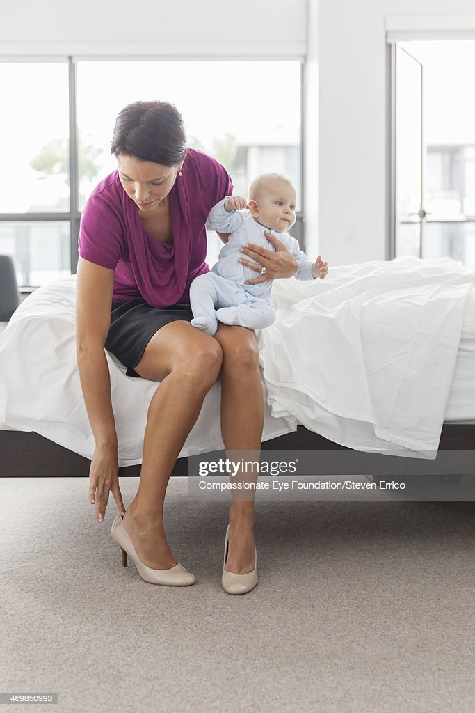 Mother sitting on bed holding baby son