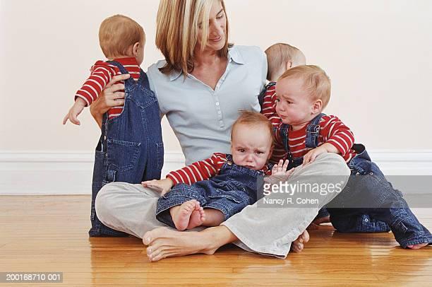 Mother sitting on hardwood floor with quadruplet babies (9-12 months)