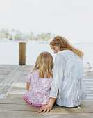 Mother sitting on jetty with daughter (3-5) rear view