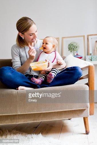Mother sitting on sofa, feeding baby girl