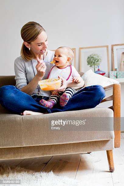 Mother sitting on sofa, feeding baby girl