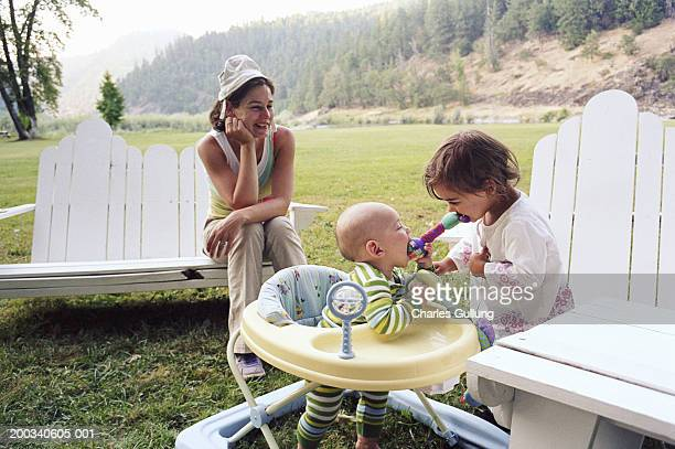 Mother sitting outdoors with children (1-3), children playing with toy