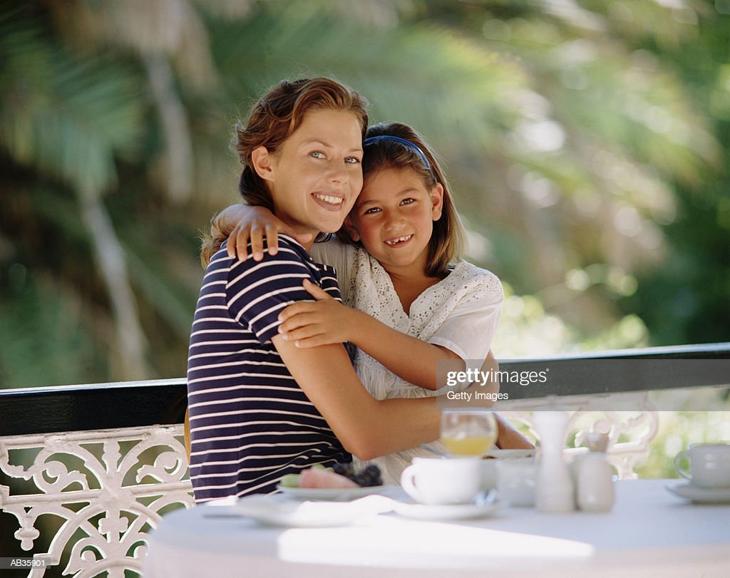 Mother sitting with daughter (7-9)on lap : Stock Photo
