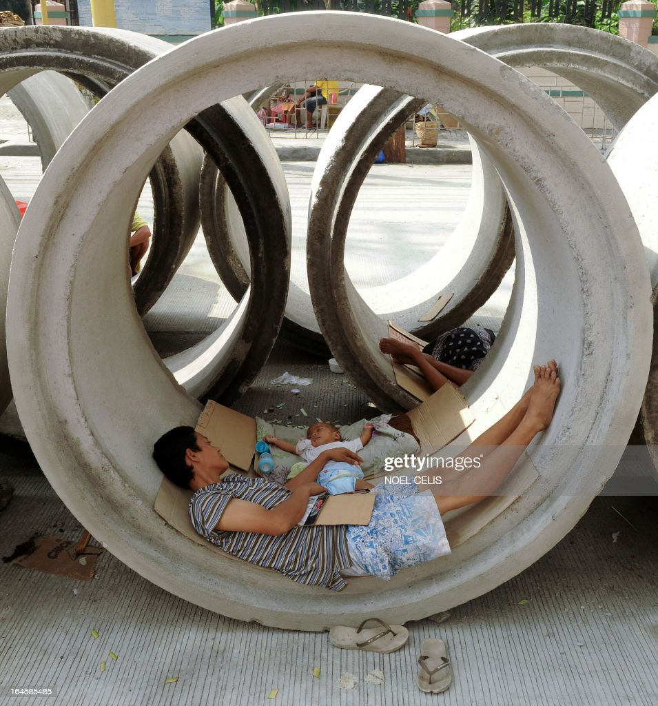 A mother sleeps beside her baby in a concrete pipe in Manila on March 25, 2013. Optimism is soaring that the Philippines is finally becoming an Asian tiger economy, but critics caution a tiny elite that has long dominated is amassing most of the new wealth while the poor miss out.