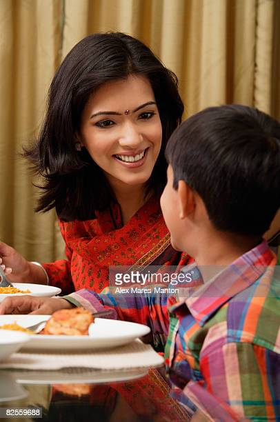 mother smiles to son at dinner table