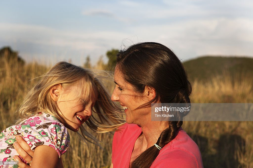 Mother smiling and playing with daughter in field : Stock Photo