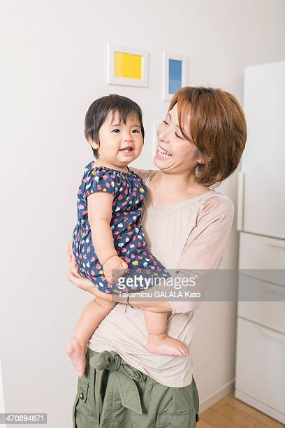 Mother smiling at baby in arms