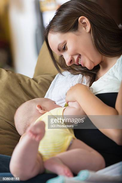 Mother smiling at baby while breastfeeding