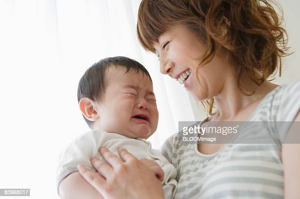 Mother smiling at crying baby, close up