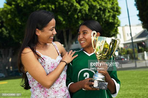 Mother smiling at daughter (11-13) holding football trophy