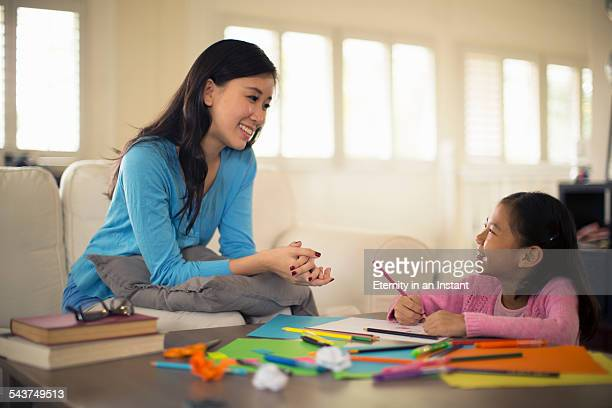 Mother smiling at daughter whilst colouring