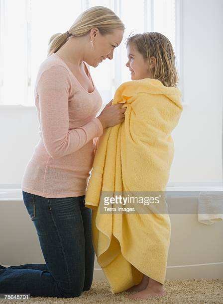 Mother smiling at daughter wrapped in towel
