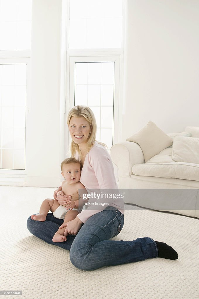 A mother smiling holding her baby : Stock Photo