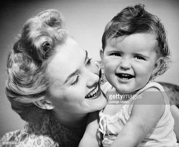 Mother smiling to baby girl (12-18 months), (B&W), close-up