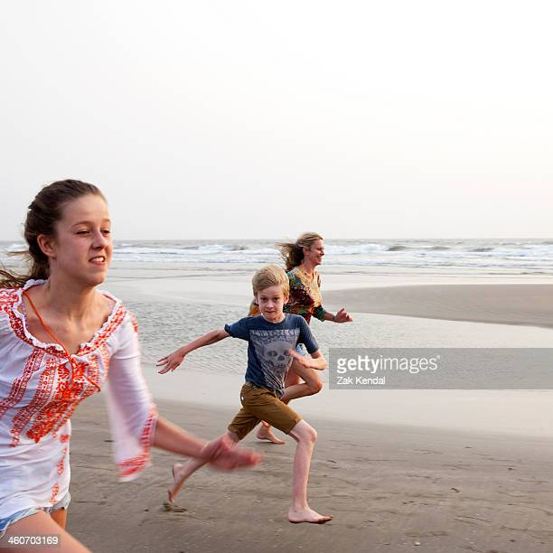 Mother, son and daughter running on beach