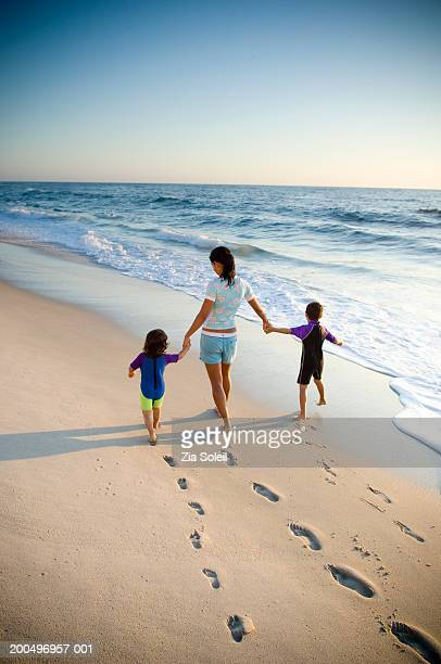 Mother, son (4-6) and daughter (2-4) walking on beach near surf