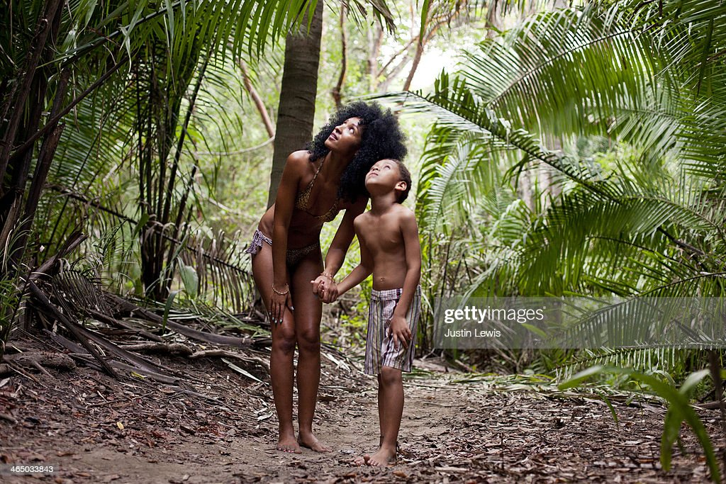 Mother & son looking into tropical trees on trail
