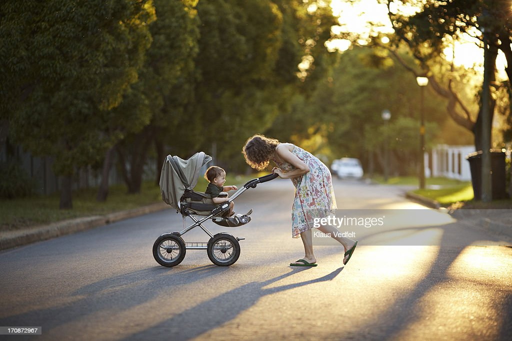 Mother & son walking with stroller in the sunset : ストックフォト