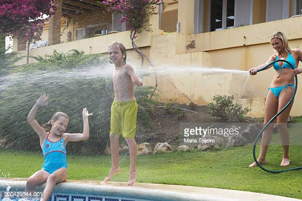 Mother spraying children (9-11) by pool with hose, portrait of boy