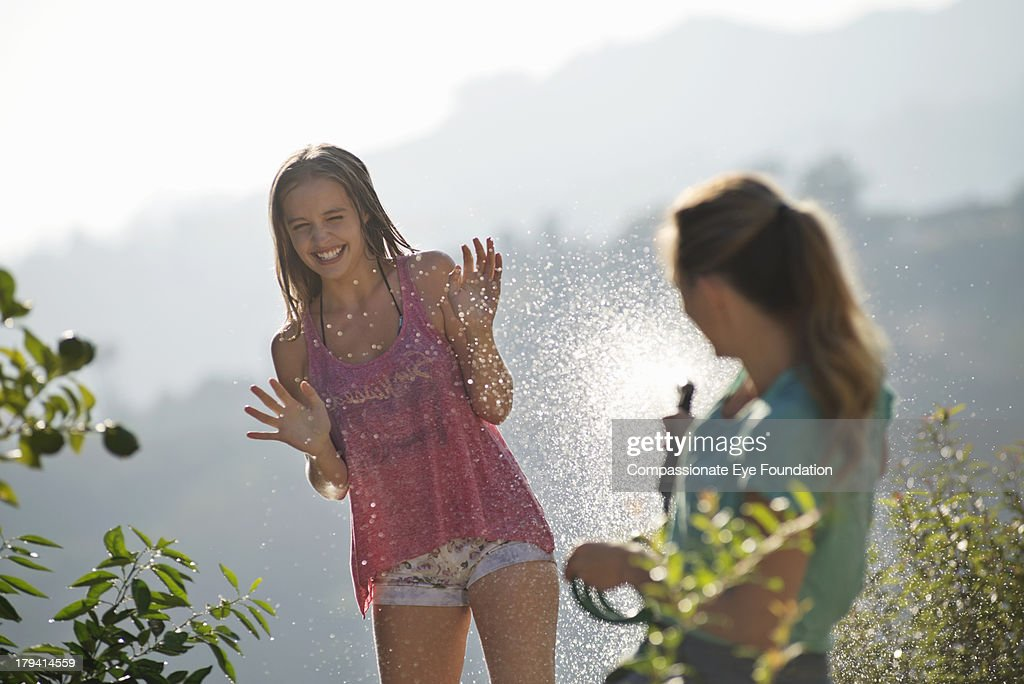 Mother spraying daughter with water in garden : Stock Photo