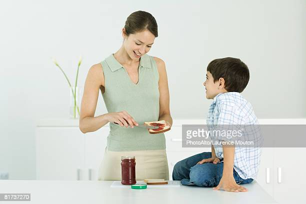Mother spreading jam on bread, chatting with young son