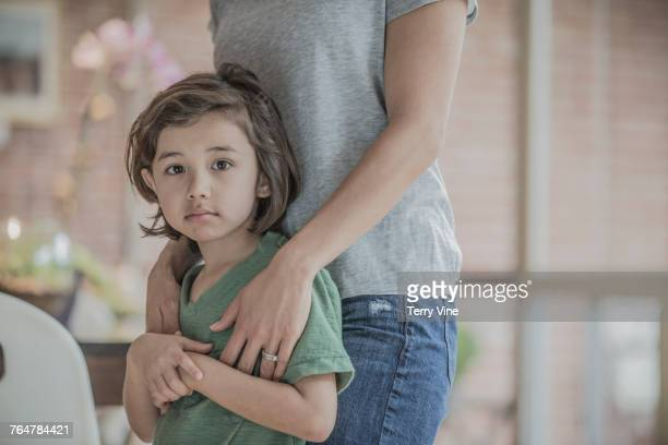 Mother standing and hugging son