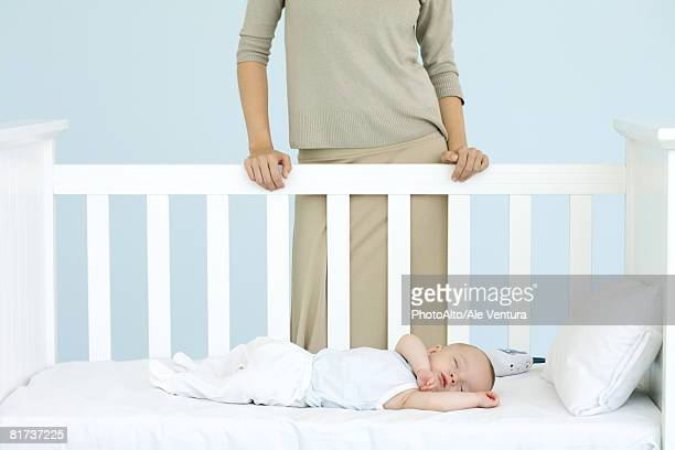 Mother standing behind crib as infant sleeps, cropped view