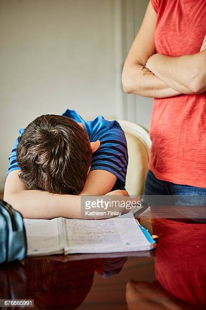 Mother standing by upset son doing homework