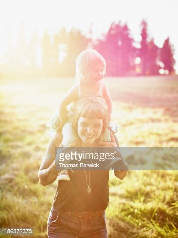 Mother standing holding toddler on shoulders
