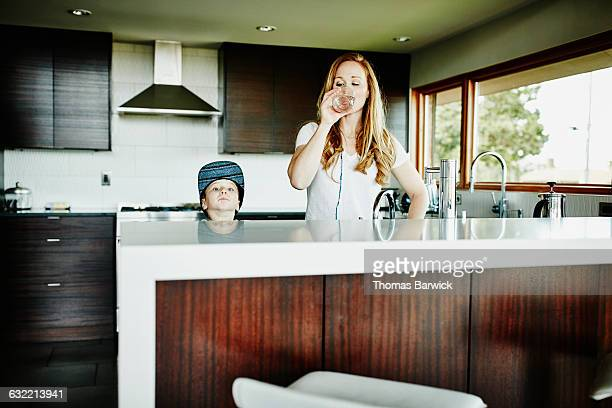 Mother standing in kitchen drinking water