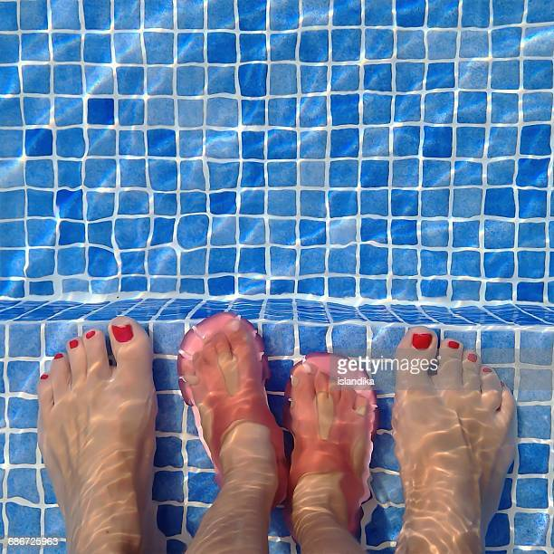 Mother standing in swimming pool with her daughter