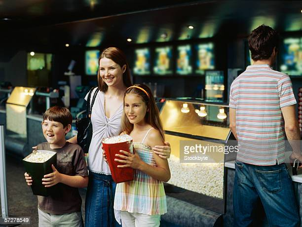 Mother standing with her son and daughter holding buckets of popcorn