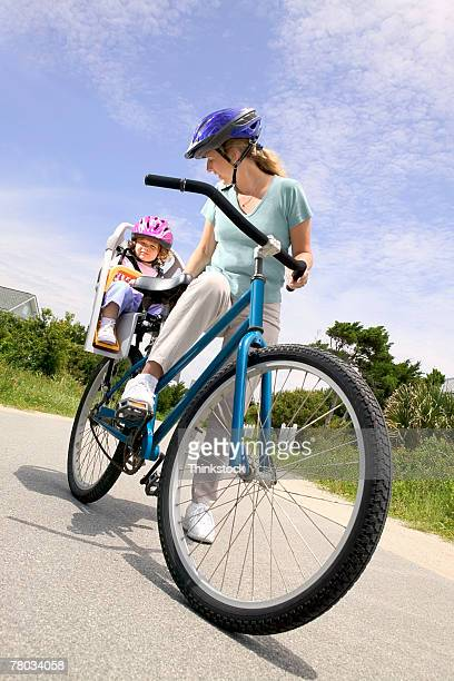 A mother stands checking her daughter's safety seat on the bicycle