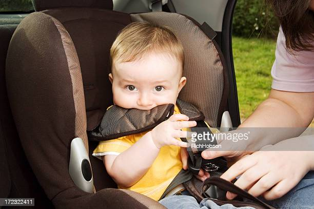 A mother strapping her baby in a car seat