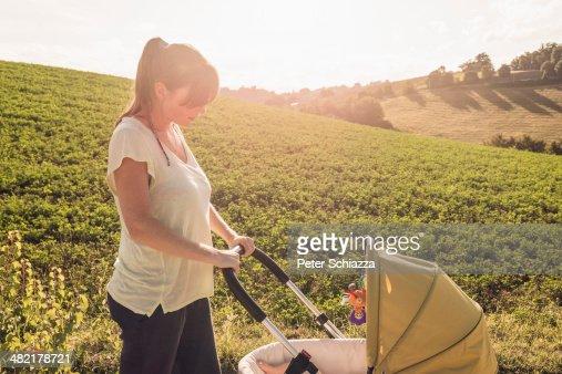 Mother strolling in countryside pushing baby pram