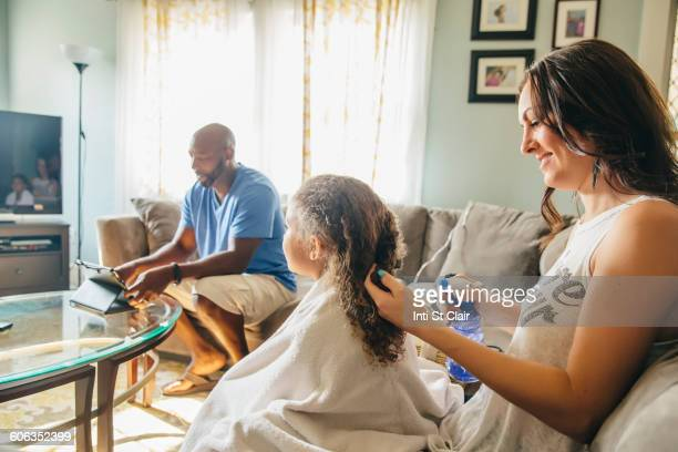 Mother styling hair for daughter in living room