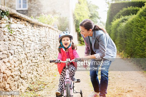 mother supports daughter who is learning cycling.