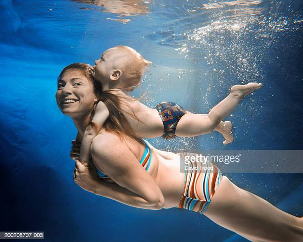 Mother swimming with baby boy(12-15 months) on back, underwater view