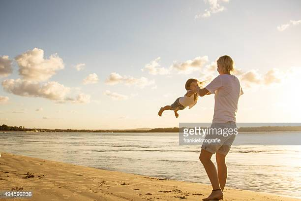 Mother swinging her child in the air