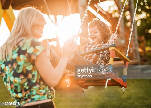 Mother swinging her happy son at sunset.