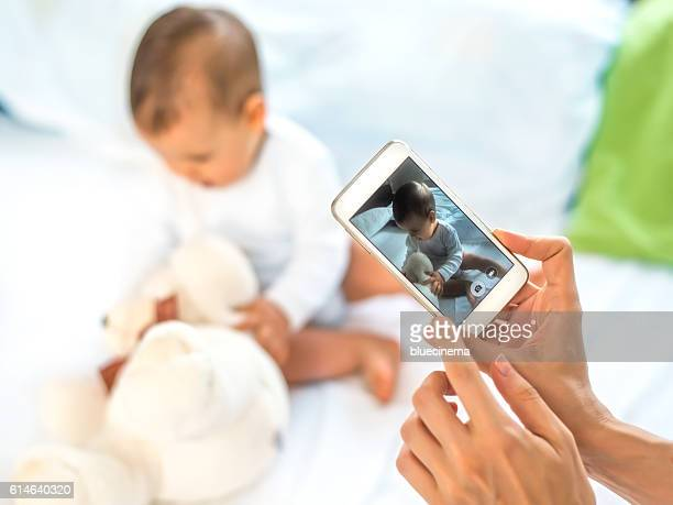 Mother take a photo of her baby