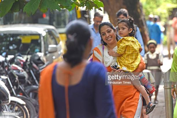 A mother takes her daughter on the first day of her school after a summer vacation at Raja Shivaji Vidyasankul Matunga on June 15 2017 in Mumbai...
