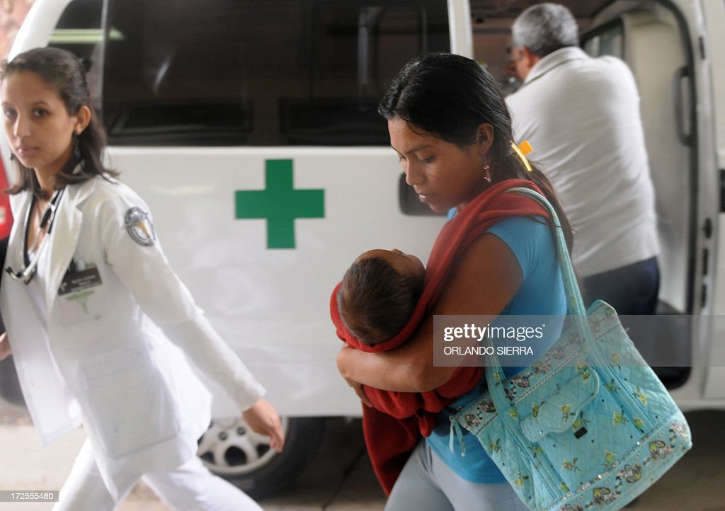 A mother takes her son with symptoms of dengue fever to be seen at Hospital Materno Infantil medical centre in Tegucigalpa on July 3, 2013. The disease vectored by the Aedes aegypti mosquito has killed ten people in Honduras so far this year. AFP PHOTO /Orlando SIERRA.