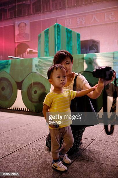 A mother takes pictures with her child in front of a mockup banner depicting a tank in Tiananmen Square during the 25th anniversary of the Tiananmen...