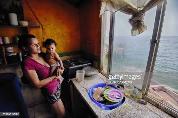 A mother takes up her baby in a house at Palafitos de Santa Rosa de Agua neighborhood on the banks of Maracaibo bay in Maracaibo city on April 28...
