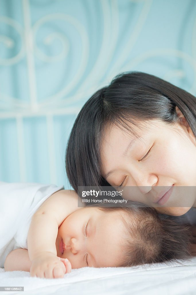 Mother taking a nap with baby : Stock Photo