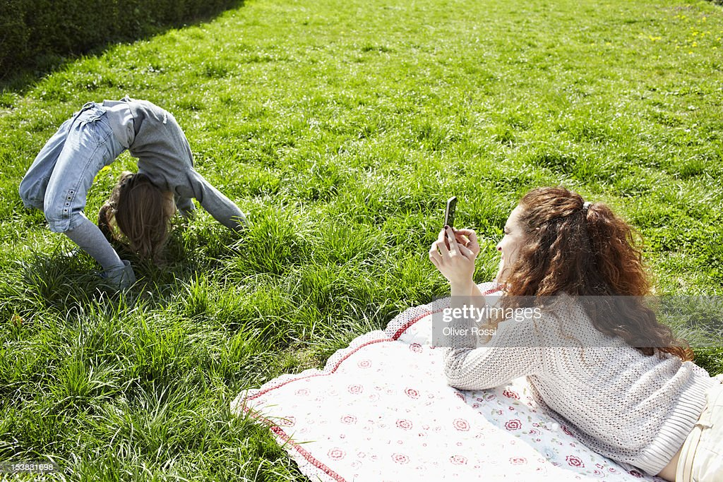 Mother taking a picture of her daughter : Stock Photo