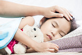 Mother taking care asian child girl while she sleeping in the bed