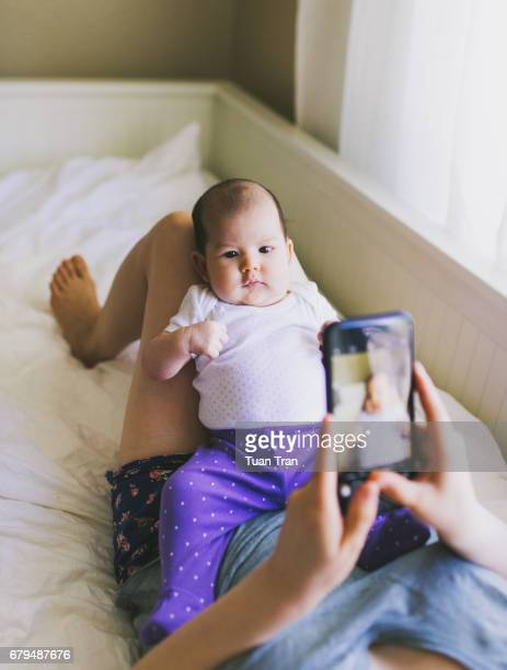 Mother taking photo of baby girl