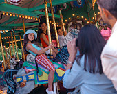 Mother taking photo of children on carousel
